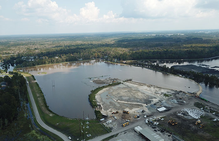 Aerial view of Grainger's Ash Pond 1, which has been filled with water to equalize pressure on the dike from the rising waters of the Waccamaw River. In the foreground, mounds of stone and bags filled with stone are assembled.