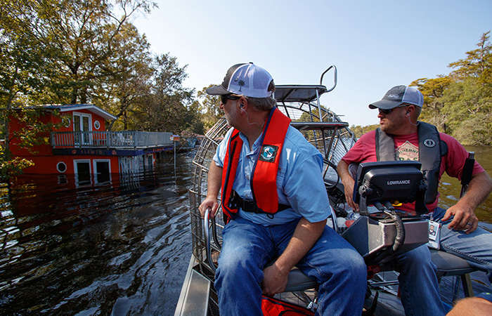 Crews with Biological Services inspect the damage already done as the  Waccamaw River over flows its banks Friday, Sept. 21, 2018 in Conway.