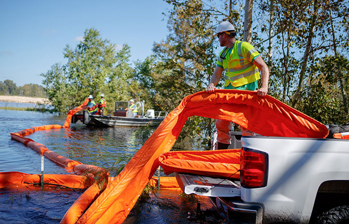Santee Cooper crews deploy floating booms around the banks of the Grainger ash ponds.